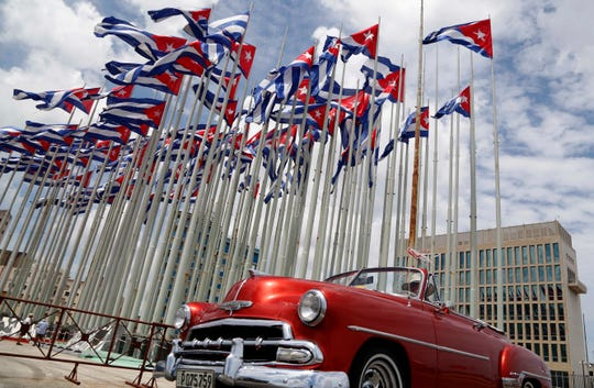 A classic American convertible car passes beside the United States embassy as Cuban flags fly at the Anti-Imperialist Tribune, a massive stage on the Malecon seaside promenade in Havana, Cuba.