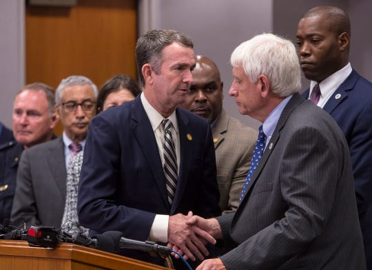 Virginia Gov. Ralph Northam , center, shakes the hand of Virginia Beach  Mayor Bobby Dyer after giving remarks during a news conference regarding the shooting at a municipal building,Friday, May 31, 2019, in Virginia Beach.