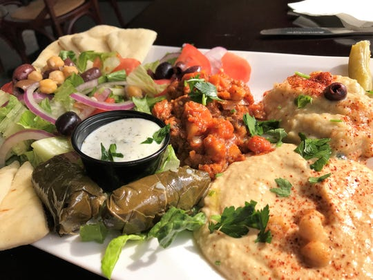A salad plate at Kabob Xpress contains, clockwise from upper left, Greek salad with pita, eggplant salad, baba gannoush, hummus, and stuffed grape leaves with yogurt sauce.