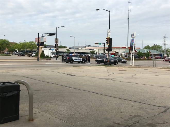 Fond du Lac police block off part of East Johnson Street on Tuesday morning as they respond to a report of a man with a knife barricaded inside a home with three children.