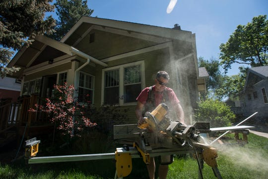 Front Country Carpentry's Chris Swetnam cuts trim in the front yard while helping to remodel a home on the 300 block South Grant Street on Tuesday on South Grant Street in Fort Collins.