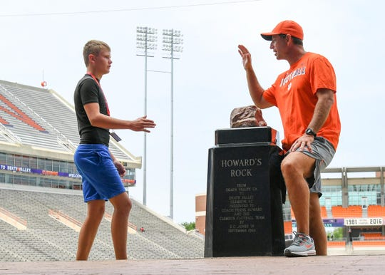 Camper Elijah Duer of Santa Rosa Beach, Florida walks up to Clemson football coach Dabo Swinney before posing for a photo at Howard's Rock during a high school group week at Dabo Swinney Football Camp in Clemson Tuesday. Nearly 800 campers had their photo taken with the coach.