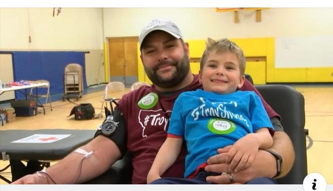"""Wes Ross gives blood while holding his 4-year-old son, Troy. The """"TroyStrong"""" Montana Red Cross blood drive takes place soon at various locations across the Treasure State."""