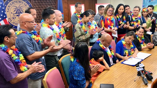"Gov. Lou Leon Guerrero signs on June 4, 2019 a proclamation declaring June ""LGBTQ Month"" and in recognition of the 50th anniversary of the Stonewall uprising that became the modern-day civil rights movement for equal rights for lesbian, gay, bisexual, transgender and queer people. Looking on and applauding are Lt. Gov. Joshua Tenorio, the first openly gay lieutenant governor in the nation, and other LGBTQ members of GovGuam under the Leon Guerrero-Tenorio administration."