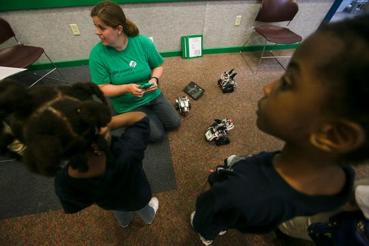 Katie Wahlstrom, middle, program manager of Girl Scouts of Central Indiana, shows Tete Minatagbe, left, and Cecil Khadijah Diakite Kariessy how to use the remote control robots at the Math and Science Center at Camp Dellwood in Indianapolis on May 29.