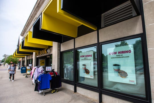 """""""Now Hiring"""" signs for a new Dunkin' location hang in windows at Iowa Book, Monday, June 3, 2019, along Clinton Street, in downtown Iowa City. Dunkin', formerly Dunkin' Donuts, currently operates a standalone store in Coralville in addition to this downtown location."""