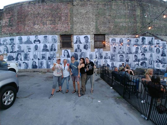 Volunteers for The Big Camera and A1LabArts pose in front of the Community Faces project at Crafty Bastard Brewery.