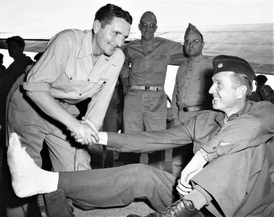 Lt. Col. Michael C. Murphy shakes hands with his borther Leo after being one of the first wo D-day casualties to reach the U.S.
