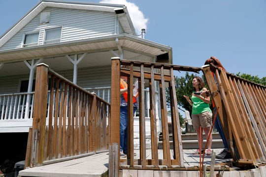 "Jackie Hettinger, center, stands in a gap in the railing on her back patio Monday morning, June 3, 2019, as she talks to Hocking County Auditor's Office employee Christy O'Nail, left, and Hocking County Emergency Management Director Cesalie Gustefson about the damage caused by an EF2 tornado to her home on Union Road near Laurelville. Hettinger said she considered herself lucky as she only had damage to soffits of her house, a broken window and damage to her deck. Some of her neighbors homes and out buildings were destroyed or heavily damaged. ""I'll never view storms the same,"" she said."