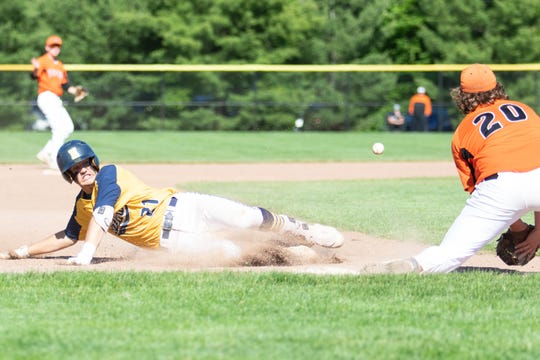 Hartland's Logan Tobel slides into third base with a run-scoring triple in a 6-5 loss to Fenton in a district championship game on Monday, June 3, 2019.