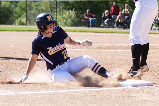 Hartland's Delaney Robeson slides into third base in a 12-2 victory over Milford in the district championship game on Monday, June 3, 2019.