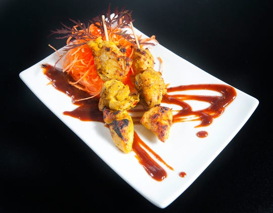 "Eatz' chicken ""saute"" is made with chicken pieces that have been marinaded in yellow curry and lemongrass then skewered and grilled. ItThe skewers are served over a spicy hoisin ans sriracha dipping sauce. The dish is garnished with carrots and a Japanese maple leaf.
