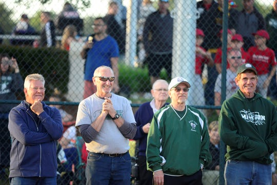 Fellow board members of Madison Summer Baseball/Softball League listen to remarks made by board member Dave Miller before new lights for a softball field were turned on for the first time on June 3, 2019.