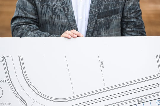 Josh Roman, Vice-Mayor of Lakeland, stands behind a printout of one of the plans for The Lake District during a media event at the site of the future development, June 04, 2019.