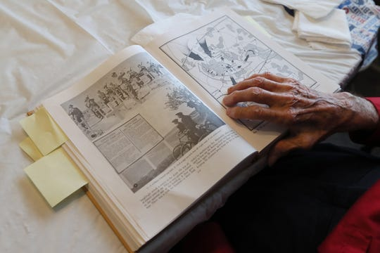 William Sidney Crawley, 95, who served in the Army during WWII, flips through a historical book he has bookmarked in sections from his own service. Crawley fought on the front lines through Germany and France after enlisting as a 18-year-old.