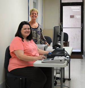 Baxter County Collector Teresa Smith (standing) and chief deputy Yvette Sigafus inspect one of the office's temporary work spaces set up in the basement of the Baxter County Courthouse on Monday afternoon.