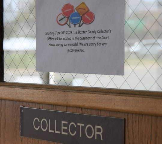 A sign on the door to the Baxter County Collector's Office informs the reader that the office will be relocating to the Baxter County Courthouse basement starting Monday.