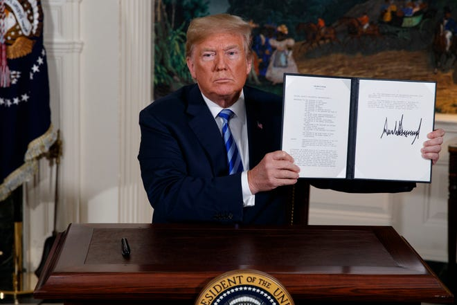 FILE - In this May 8, 2018 file photo President Donald Trump shows a signed Presidential Memorandum after delivering a statement on the Iran nuclear deal from the Diplomatic Reception Room of the White House.
