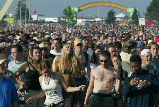"Fans dance as the rock band Phish performs during the first day the band's two-day ""It"" festival Saturday, Aug. 2, 2003, before a crowd estimated at 60,000 at the former Loring Air Force Base in Limestone, Maine."