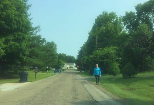 A pedestrian walks along the east side of Oak Meadow Drive the morning of June 4.