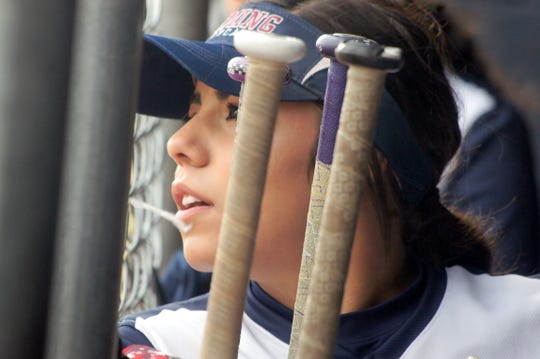 Lady 'Cat graduate Mireya Trujillo waits by the bat rack for her turn at the plate.