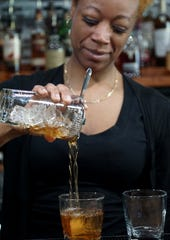 The Loft Cigar Lounge bartender Roni McKnight pours her version of a Manhattan for a customer on June 3.