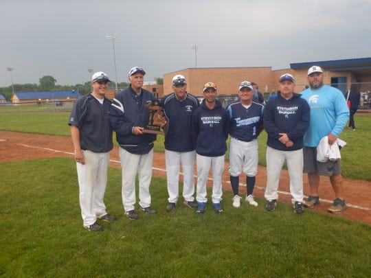 The Livonia Stevenson baseball coaching staff, led by coach Rick Berryman (second from left), poses after winning the 2019 district title.