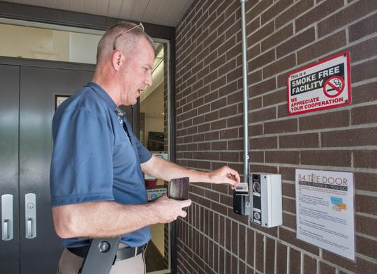 Daniel Hahn, Santa Rosa County School District director of safety, shows his ID at the single point of access outside the entrance to  Bennett C Russell Elementary School in Milton on Tuesday, June 4, 2019.  Once approved, the door will be unlocked and the visitor will then sign in at the front desk.