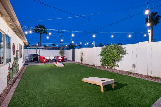Cafe lights and artificial turf give the yard a more contemporary feel and reduce maintenance.