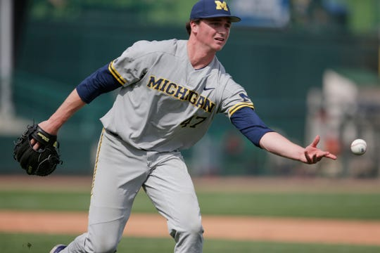 Michigan pitcher Tommy Henry tosses the ball to first base for an out against Nebraska's Alex Henwood during the fourth inning of an NCAA college baseball game in Lincoln, Neb., Friday, May 17, 2019.
