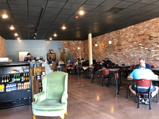 Inside Ancestor Coffeehouse & Creperie, which has plenty of seating and a modern setting crossed with a brick facade.