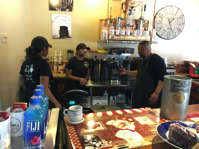 Derrod Boone works behind the counter at his Jacobus eatery with two of his daughters, Brittany, left, and Destiny. Another daughter, Trinity, works there, too, as does his fiancé, Jen Sherman. Boone's Vintage Café and Greybeards Antiques operate in the former Leader Furniture building.