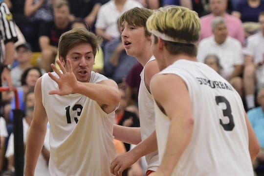 York Suburban's Nate Bowman reaches out to slap hands with setter Noah Chojnacki after the Trojans scored a point in a PIAA Class 2A boys' volleyball semifinal June 4.