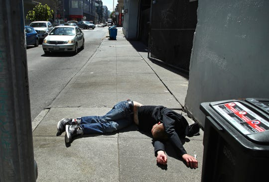 FILE - In this April 26, 2018, file photo, a man lies on the sidewalk beside a recyclable trash bin in San Francisco. San Francisco supervisors consider legislation Tuesday, June 4, 2019, allowing the city to force mentally ill drug addicts into housing and treatment for up to a year. Mayor London Breed says it's inhumane to let addicts languish on the streets, but homeless advocates say the measure is extreme and a violation of civil rights. (AP Photo/Ben Margot, File)