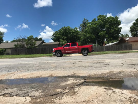 A red pickup drives over a cracked portion of College Hills Blvd. Tuesday, June 4, 2019.