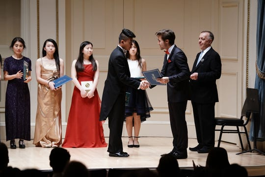 Jack Williams (Zhi Jie Yang)'s accepting a certificate at the 2019 American Protege International Piano and Strings Competition at Weill Recital Hall at Carnegie Hall in New York last month.