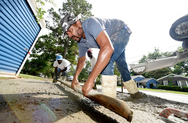 Joseph Nelson works on a concrete drive in Shreveport, Tuesday, June 4, 2019.