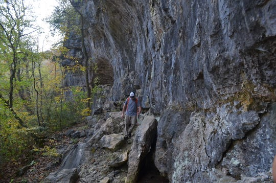 Parks employee Clinton Barnett hikes along Coon Den Bluff at Bryant Creek State Park.