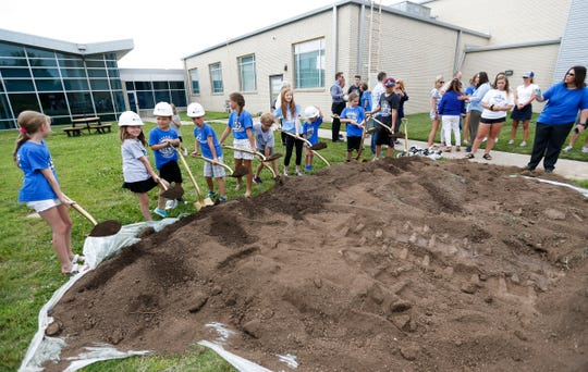 Greenwood Laboratory School students turn dirt during a groundbreaking ceremony for an expansion to the school on Tuesday, June 4, 2019.