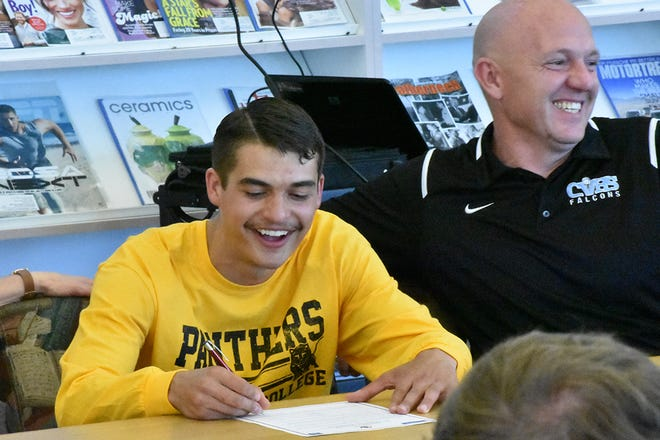 Canyon View's Mason Lyman signs his letter of intent while his coach Robbie Potter looks on.