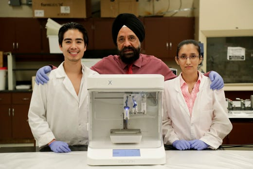 Florida A&M University Professor of Pharmacy Mandip Sachdeva, center, has worked with his students Paul Dinh, left, an undergraduate studying biology and Shallu Kutlehria, a PhD student studying pharmaceutics, to create the first 3D printed human cornea in the United States. The cornea is made using the Cellini Bio X bio printing machine.