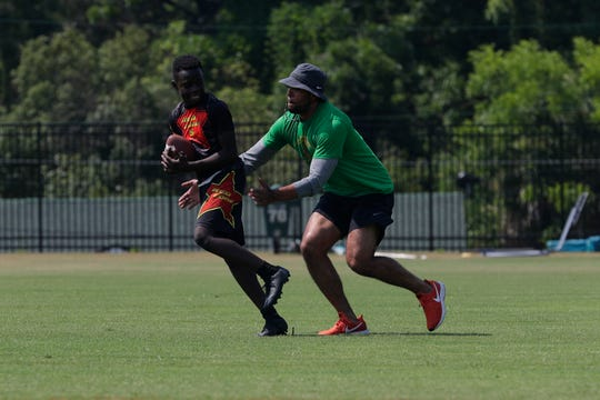 Zion Paret, 12, gets tagged by FAMU defensive backs coach Brandon Sharp during a session at the Junior Rattlers Football Camp on Tuesday, June 4, 2019.