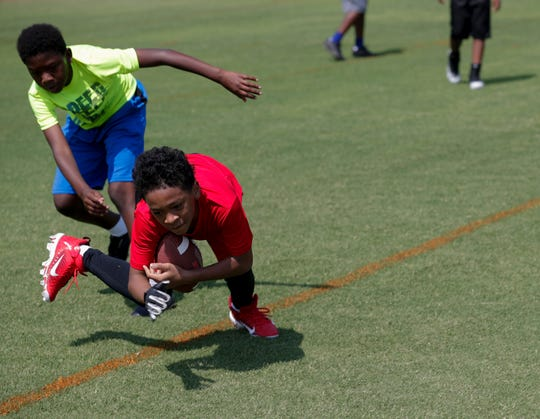 Axel Thomas, 11, lunges by Delphone Lucas, 10, during the Junior Rattlers Football Camp.