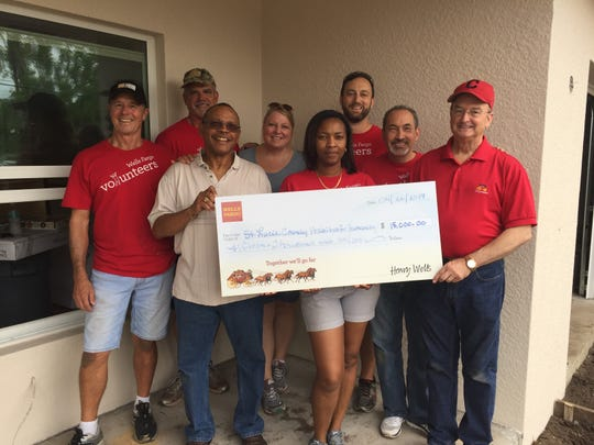 Meade Rankin, left, Jim Braxton, Lee Brown, Sandy Seese, Shelly Thomas, Richard Giessert, Ademil Castrillo, Earl Morgan hold a $15,000 check from Wells Fargo to the St. Lucie County Habitat for Humanity.