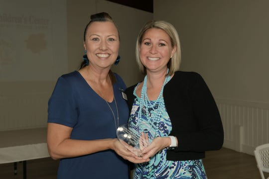 Martin County Guild President Heidi Monsour, left, presents volunteer Michelle Schwartz with her award.