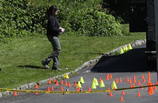 An FBI agent walks by small cone indicating spent shells in the back lot of the Ardsley Acres Motel on Saw Mill River Road in Ardsley June 4,  2019. An overnight drug raid left a suspect dead and two police officers wounded.