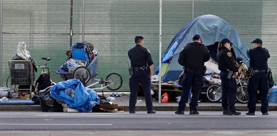In this March 1, 2016, file photo, San Francisco police officers wait while homeless people collect their belongings in San Francisco. San Francisco supervisors are considering legislation Tuesday, June 4, 2019, allowing the city to force mentally ill drug addicts into housing and treatment for up to a year.