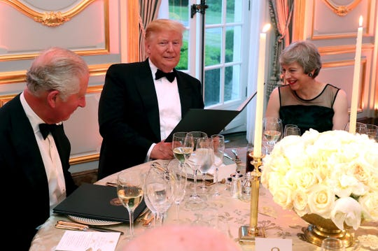 President Donald Trump is flanked by British Prime Minister Theresa May and Prince Charles at a dinner he and first lady Melania Trump hosted at Winfield House during their state visit.