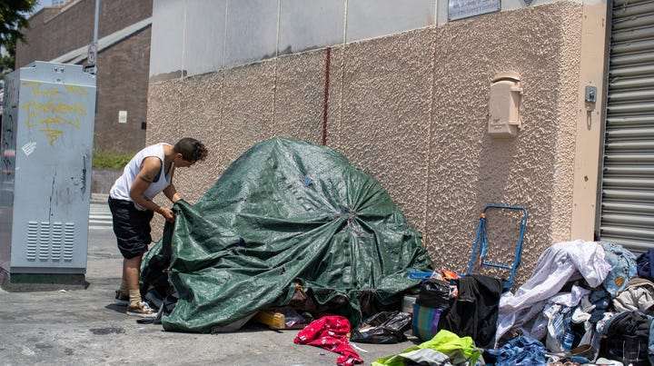 A homeless man adjusts his tent on a street in downtown Los Angeles