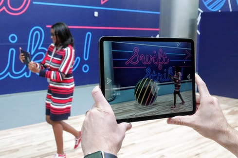 In Apple's augmented reality bowling game, a WWDC attendee uses the phone to roll an animated ball.